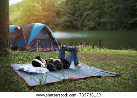 Holiday camping - Young boy resting on pallet near a tent in the forest #735738139