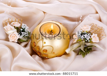 Holiday candle and flowers against a background of silk - stock photo
