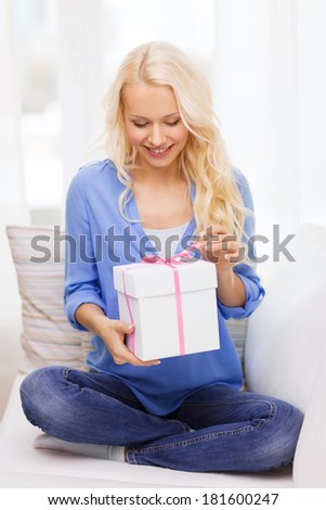 holiday, celebration, home and birthday concept - smiling young woman with gift box at home