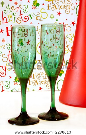 Holiday Cheer - Two green wine glasses and a red wine bottle with a cheerful holiday background.