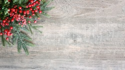 Holiday Christmas Background with Evergreen Pine Tree Needles and Red Winter Berries Over Wood Texture, Horizontal, Widescreen