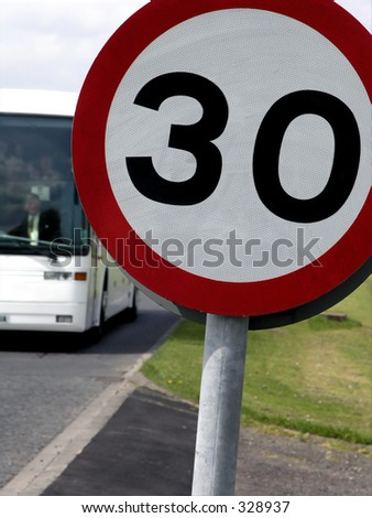 Holiday coach approaches traffic speed limit sign.