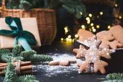 Holiday composition of tasty homemade cookies, gift hamper, gift and garland on black. Christmas vibes. Happy New Year.