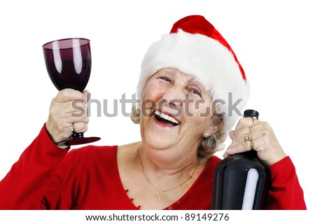 Holiday concept: smiling senior woman or grandmother is wearing Santa Claus's hat and having lots of fun drinking at the Christmas party