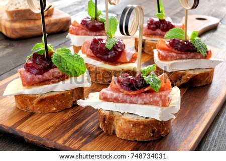 Holiday crostini appetizers with cranberry sauce, brie, salami, and mint on a wooden server