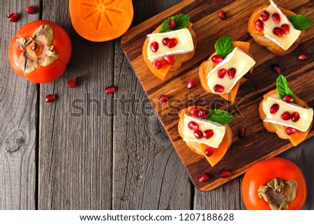 Holiday crostini appetizers with persimmons, pomegranates and brie cheese. Top view scene on a wood background.