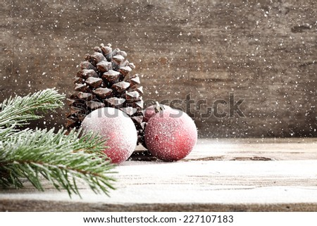 holiday decoration on wooden sill and decoration of red balls and cone and tree