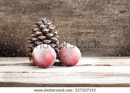 holiday decoration on wooden sill and red balls and brown cone space