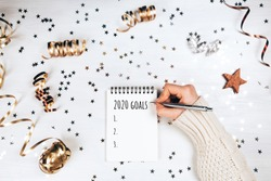 Holiday decorations and notebook with 2020 goals on white table, flat lay style. Christmas planning concept.