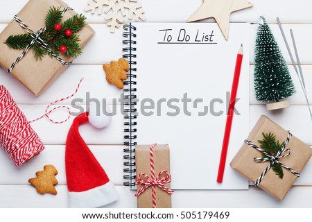 Holiday decorations, gift, present box, miniature fir tree and notebook with to do list on white wooden table from above. Christmas or winter planning concept. Flat lay style.