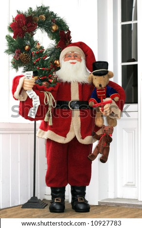 holiday decorations with santa holding toys and wreath on front door step