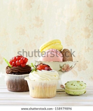 holiday desserts, cupcakes and macaroons on a vintage background