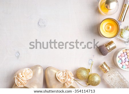 Holiday feminine cosmetic background in gold colour. Cosmetic objects: gold heels, christmas balls, glitter nail polish, perfume, burning candle, meteorites blush, brush. Getting ready for a party
