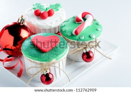 Holiday festive christmas theme mini cup cakes with shiny decorative balls and ribbons - stock photo