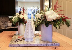 Holiday Floral center pieces with white roses, red accents and greenery on a large butcher block and white granite kitchen island