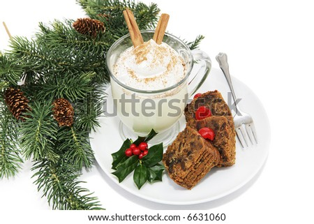 Holiday fruitcake and eggnog on a plate garnished with holly and surrounded by pine branches.  White background.