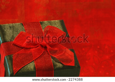 Holiday Gift - A pretty gift in a green fabric covered box with a red gossamer ribbon and bow for a special person.