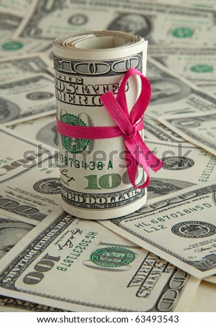 Holiday gift of money. 100 dollar bills with pink satin ribbon.