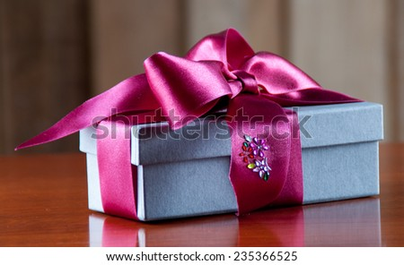 Holiday Gift Packed into Grey Box with Purple Ribbon on Glossy Wooden Table