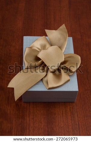 Holiday Gift Packed into Grey Box with Ribbon on Glossy Wooden Table. Design elements.