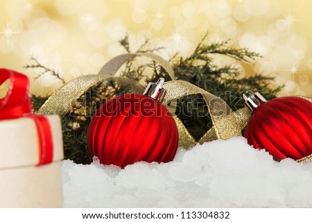 Holiday gift with christmas eve branch in snow. New year traditional decoration with ribbons and red ball