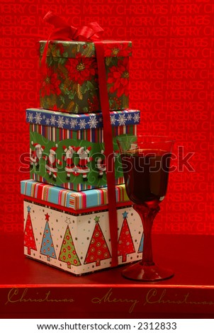 Holiday Gifts - Festive gift boxes and a glass of merlot wine against a cheerful holiday background.