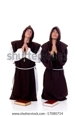 Holiday Halloween scene, two priests in habit praying.  Studio, white background.