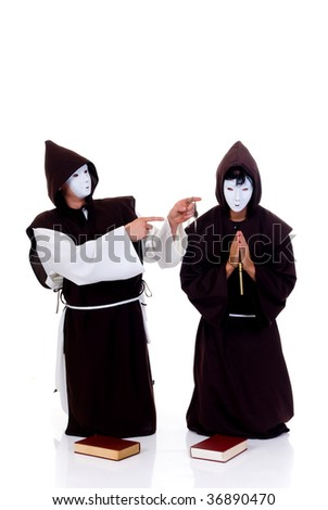 Holiday Halloween scene, two priests in habit with white mask.  Studio, bleached background.
