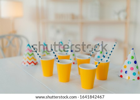 Holiday hats and paper cups with beverage and straws on white table. Festive event. Birthday party celebration concept. Blurred background. Nobody on picture
