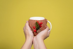 Holiday mug in cozy knitted cup holder with christmas decorations for winter hot tea or coffee or cocoa in hands of woman with beautiful festive pink manicure.