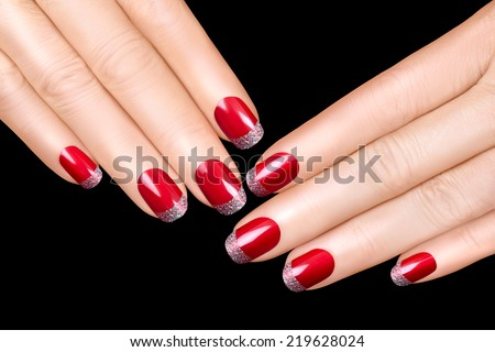 Holiday Nail Art. Luxury nail polish with glitter French manicure. Manicure and makeup concept. Closeup hands isolated on black background