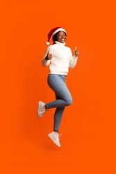 Holiday Offer. Joyful Black Santa Lady In Christmas Hat Jumping And Showing Thumb Up Gesture, Recommending Something, Having Fun On Orange Background In Studio, Cheering Xmas And New Year, Copy Space
