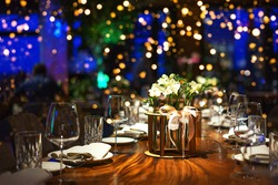 Holiday party blurred background made from decorated table with bouquet of flowers and colorful lights bokeh. Selective focus. Christmas dinner, New Year, Birthday, Wedding Party table setting.