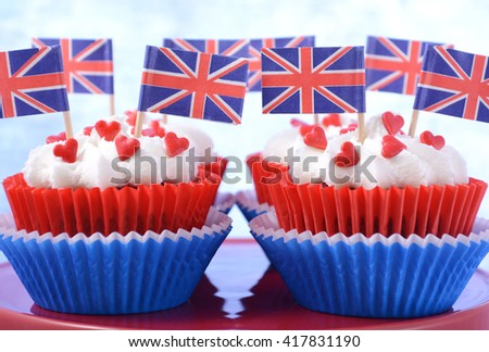 Holiday party cupcakes with UK flags on red cake stand on large flag.