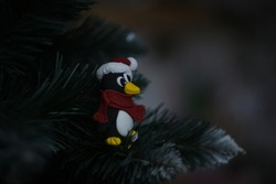holiday penguin in a santa claus  hat with pompon and red scarf sits on branch of the christmas tree and looks sideways