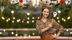 holiday, photo booth and people concept - happy smiling woman in halloween costume of leopard with ears and scull party accessory over roof top background