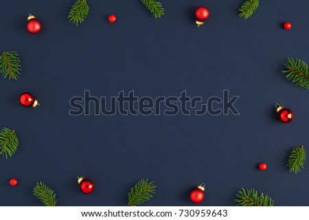 Holiday postcard. Xmas frame branches decorations in the red balls and red beads on a dark blue background. Ready Christmas background for your text  #730959643