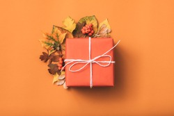 Holiday present. Greeting. Gift box. Fall leaves decorative composition. Orange background.
