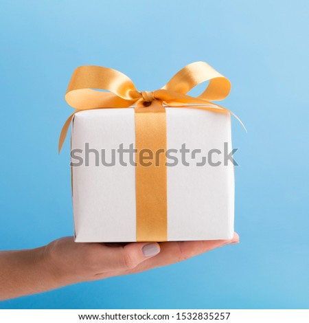 Holiday presents. Woman holding white present box with gold ribbon over blue background