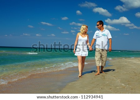 holiday romance, happy couple walking on beach