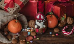Holiday Saint Nicholas,  the chocolate with gifts for children and adults on wooden background