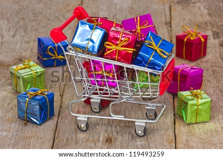 Holiday sale and shopping concept. Cart with colorful gift boxes.