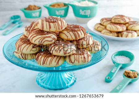 Holiday salted caramel thumbprint cookies drizzled with milk chocolate sitting on blue glass pasty stand and additional cookies on plate surrounded by ingredients in blue and white utensils