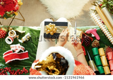 Holiday season. Upper view of trendy housewife in sparkle gold sequin santa hat sitting on divan in the modern living room at Christmas making craft present box. #1531961966