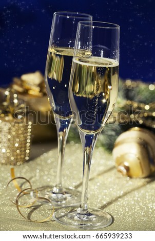 Holiday setup with sparkling wine in flute glasses and Christmas decorations #665939233