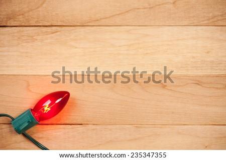 Holiday: Single Christmas Light On Wood Background