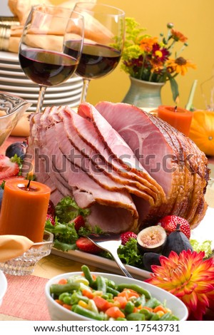 Holiday table setting with delicious whole baked sliced ham, fresh strawberries, figs, vegetable salad and glasses of red wine.