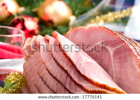Holiday table setting with delicious whole baked sliced ham, vegetable salad and glasses of red wine. Christmas decoration, candles, ornaments around.