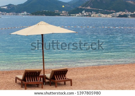 Holiday, travel and vacation concept. The empty beach with two chairs and umbrella. Sea with boats and mountains in a background #1397805980
