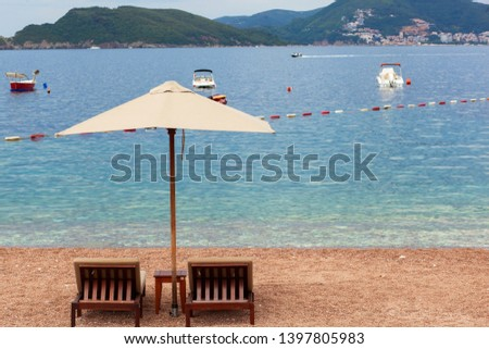 Holiday, travel and vacation concept. The empty beach with two chairs and umbrella. Sea with boats and mountains in a background #1397805983